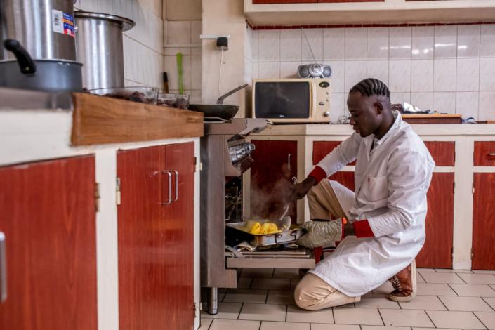 Un migrant prépare le repas pour un centre d'aide sociale